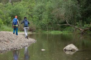 parella que fan ruta de senderisme passant per la vora d'un riu