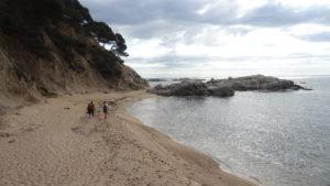dos nois que caminen per la platja i arriben cap a unes roques planes que estan a sobre el mar