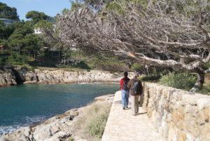 dos nois caminant pel camñi de ronda i al costat esquerra la cala d'aiguafreda