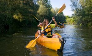 A primer pla kayak pel riu ter amb un noi i una noia, semblen joves. i a darrera un altre kayak amb una parella, semblen els pares